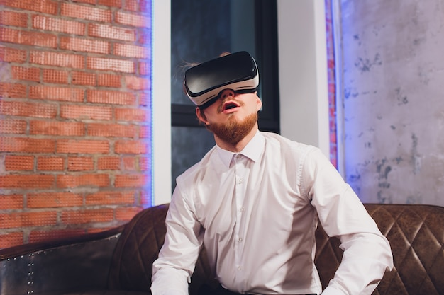 Bearded young man wearing virtual reality goggles in modern coworking studio.