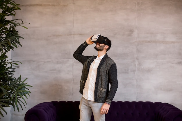 Bearded young man wearing virtual reality goggles in modern room