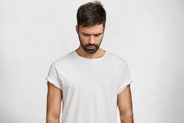 Giovane barbuto che indossa la maglietta bianca