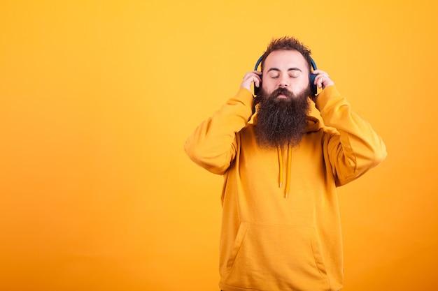 노란색 후드티를 입은 수염난 청년, 노란색 배경 위에 평화롭게 파란색 헤드폰으로 음악을 듣고 있습니다. 잘 생긴 남자. 멋진 노래.