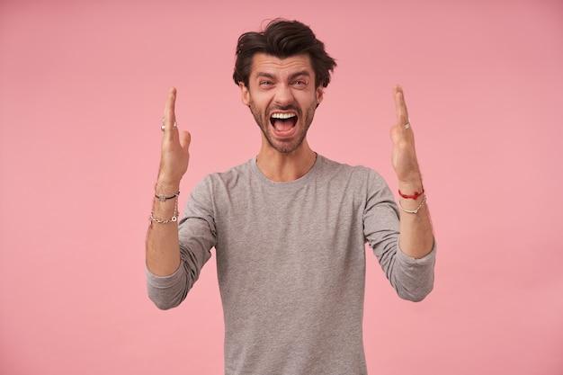 Бородатый молодой человек с темными волосами в сером свитере, стоит с поднятыми ладонями, смотрит и кричит с возбужденным лицом