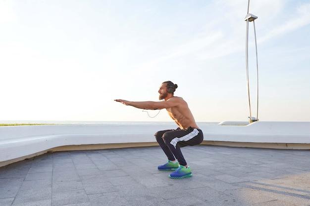 Бородатый молодой человек с подтянутым спортивным телом, делает упражнения, слушает музыку в наушниках, имеет мускулистую форму тела.