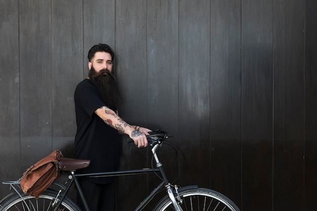Bearded young man with his bicycle in front of black wooden wall