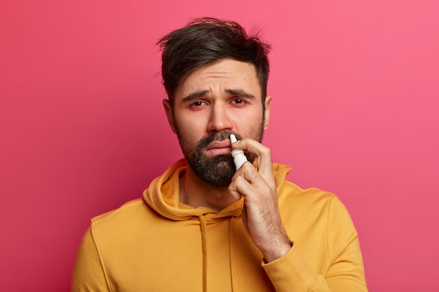 Bearded young man with red eyes, runny nose and symptoms of flu or cold, sprays nose with drops, cures epidemic, uses best remedy for stuffy nose, wears yellow sweatshirt, tries not to sneeze