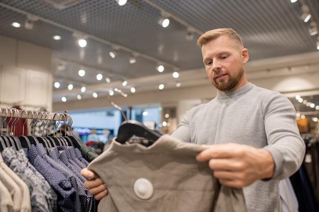Бородатый молодой человек в толстовке на вешалке выбирает новую повседневную одежду, делая покупки в торговом центре во время сезонной распродажи