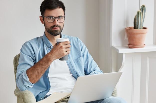 Бородатый молодой человек, работающий дома