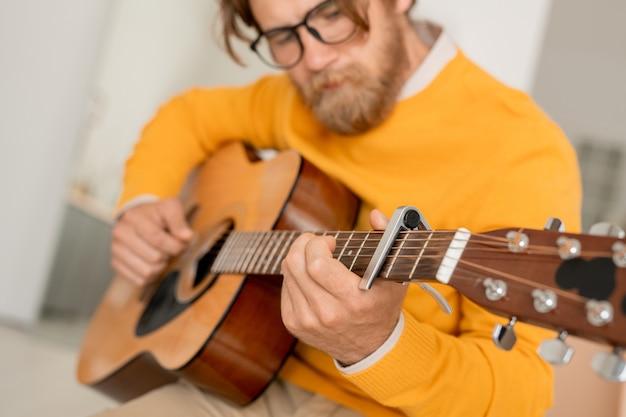 Бородатый молодой музыкант со струнным музыкальным инструментом, создающий музыку или настраивающий акустическую гитару в домашних условиях, прежде чем играть на нем