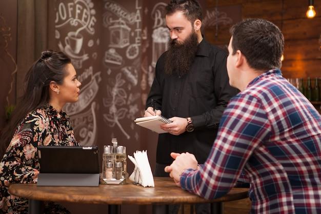 レストランで若いカップルから注文を受けているひげを生やした若いウェイター。ヴィンテージパブ。