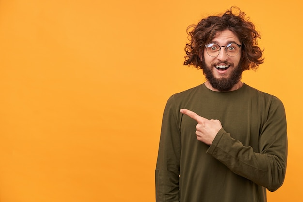 Бородатый молодой человек выглядит взволнованным, довольным, довольным, удивленным, указывая указательным пальцем в сторону