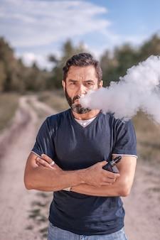森の草の上にアークを持ったひげを生やした男。タバコの代替としての電子タバコ。