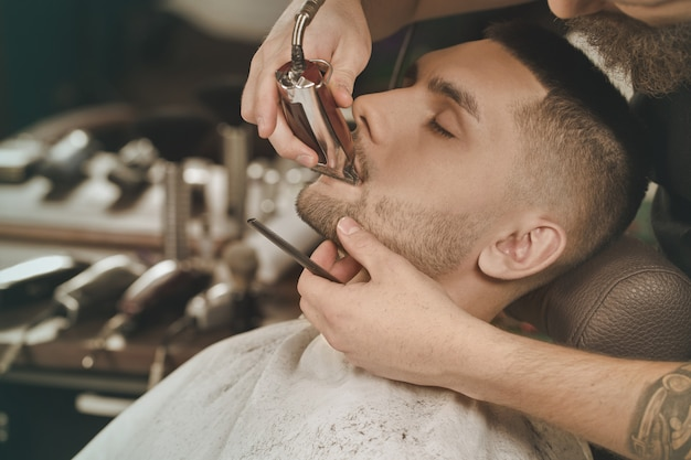 Beardlife. horizontal portrait of a young man having his beard trimmed in a barbershop