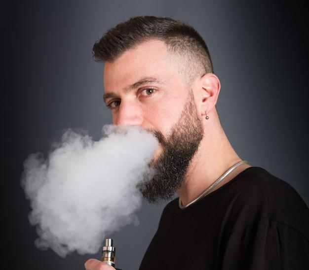 電子タバコを吸うひげを生やした男