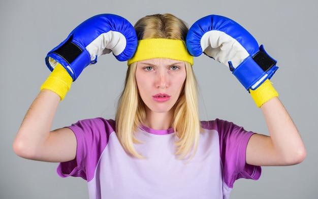 頭痛を打ち負かす。戦うのに疲れた女の子のボクシンググローブ。強い女性は痛みに苦しんでいます。女の子の痛みを伴う顔はボクシンググローブで頭を抱きしめます。頭痛の治療。頭痛の概念。落ち着いて、頭痛を取り除きます。