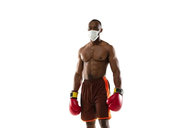 Sconfiggi il virus. pugile afroamericano in maschera protettiva, guanti.