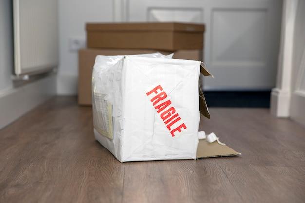 파손된 배송 상자를 깨지기 쉬운 스티커로 두드리고 집에서 파손된 배송된 판지 포장