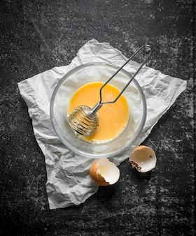 Яйцо взбить в миске венчиком на бумаге. на темной деревенской поверхности