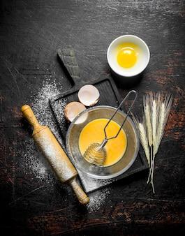 Взбить яйца венчиком в стеклянной посуде. на темной деревенской поверхности