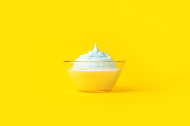 Beaten eggs with sugar in a glass plate, over yellow background, culinary concept