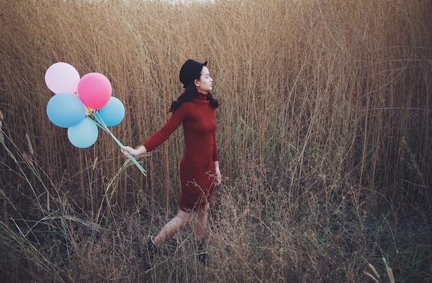 美しいアジアの女性は風船を持って、野草の美しい景色を眺めながら立っています