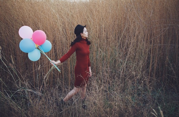 Beatiful asia woman hold balloons and standing with beautiful view of filed grass