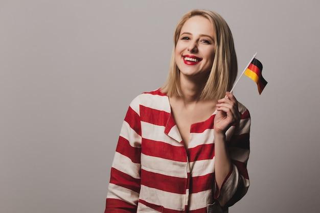 美しいブロンドの女の子は手にドイツの旗を保持します