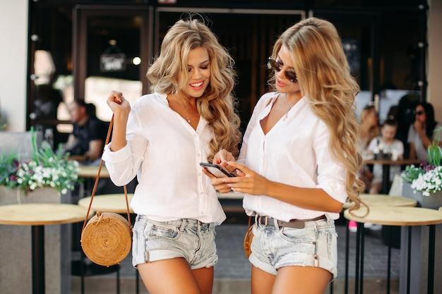 Красивые кудрявые близнецы держат смартфон на улице возле ресторана