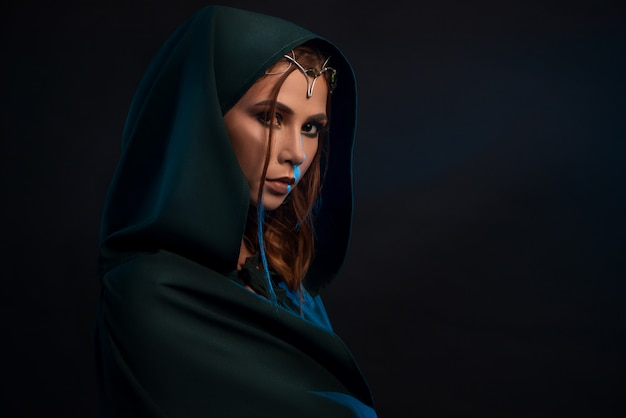 Beatiful elf princess wearing dark green cape looking at camera from darkness.