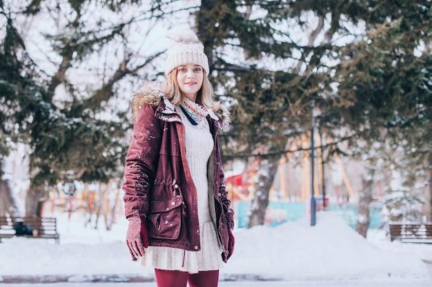 美しい女性の笑顔の肖像画。雪の冬の服を着て幸せな女の子の肖像画