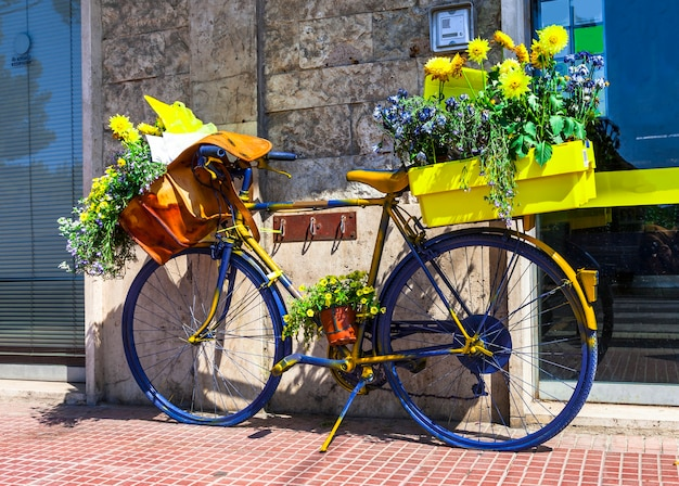 Красивое цветочное уличное украшение со старым велосипедом почтальона