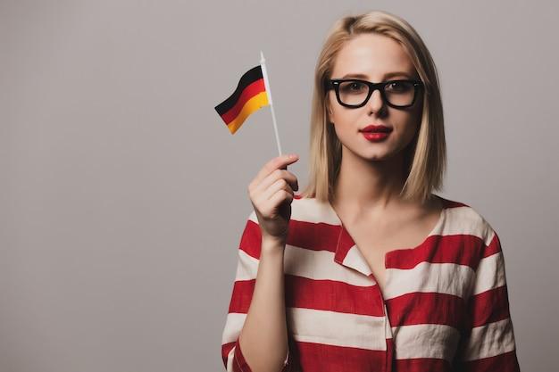 Beatiful girl in glasses holds german flag