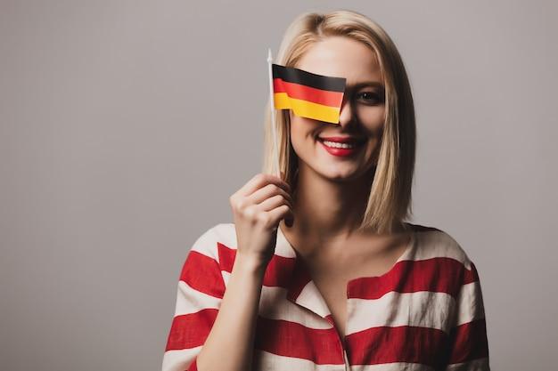美しい少女はドイツの旗を保持します