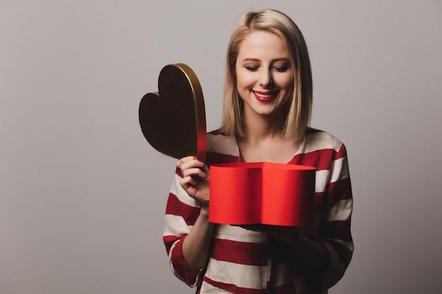Beatiful girl holds heart shape gift box
