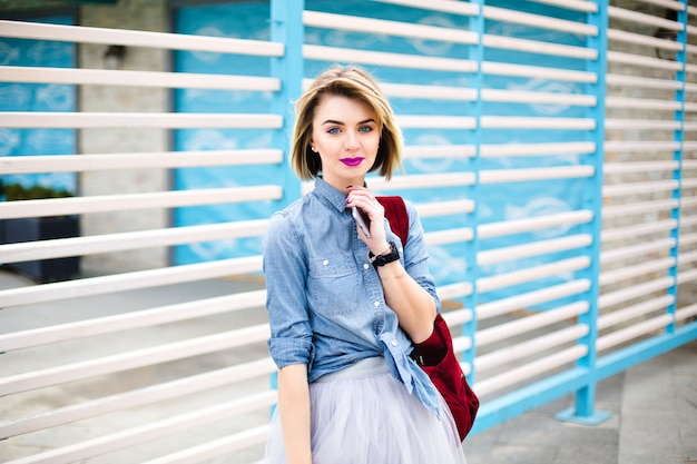 Beatiful girl with bright pink lips and tattoo on her hand holding smartphone with blue and white stripes on the background.
