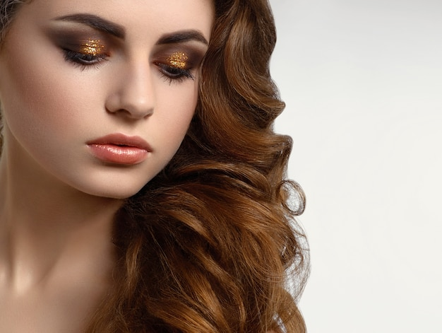 Beatiful model with brown curly hair wearing amazing evening make up