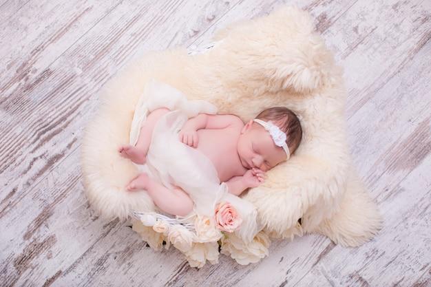 Красивая новорожденная девушка в цветочной повязке на голову