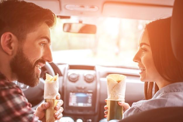 아름다운 사람들이 차에 함께 앉아 서로를 바라보고 있습니다.