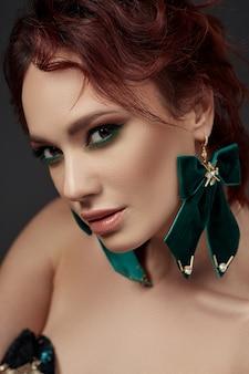 메이크업과 녹색 귀걸이와 아름 다운 빨간 머리 여자