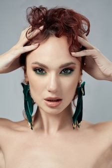 Beatiful red hair woman with make up and green earrings Premium Photo