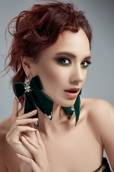 Beatiful red hair woman with make up and green earrings