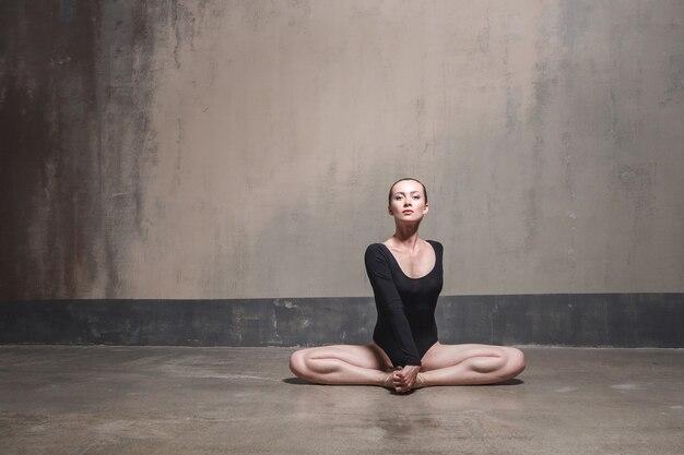 Beatiful woman sit in lotus pose and looking at camera. studio shot