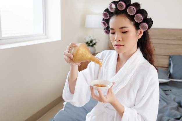 Beatiful young asian woman in bathrobe pouring sparkling golden body lotion or spa treatment in small bowl