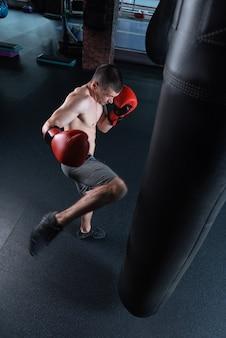 Beating bag. dark-haired jacked man wearing no shirt and grey shorts beating punching bag