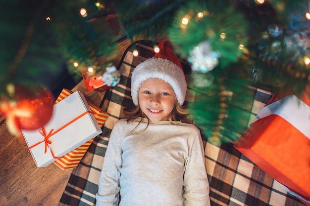 Beatufiul and positive small girl is lying under christmas tree