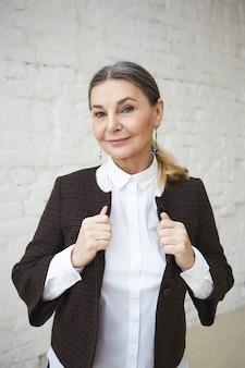 Beaty, 스타일, 패션 및 연령 개념. 실내에서 포즈를 취하는 아름다운 회색 머리 50 세 여성의 허리까지, 흰색 벽돌 벽에 서서 세련된 복장을 조정하고 회의를 갖습니다.