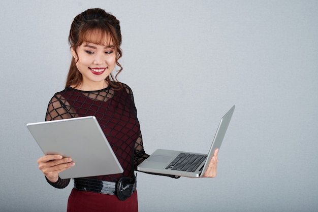 Beauitiful business woman multitasking on laptop and tablet pc