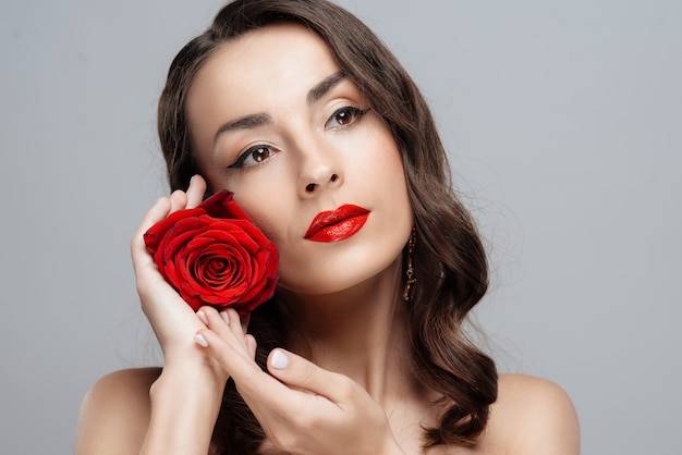 Beauteous brunette woman with red lipstick on lips.