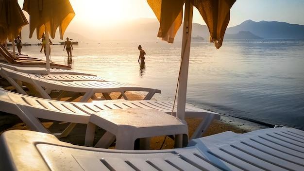 Beautfiul sunset over the sunbeds on sea beach and calm sea water.