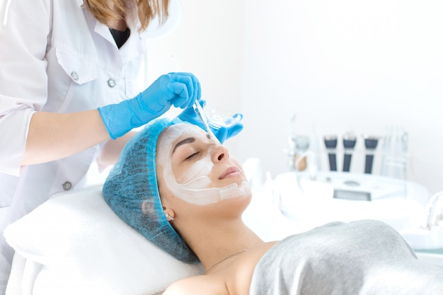 Косметолог наносит маску на лицо пациента для ухода за кожей