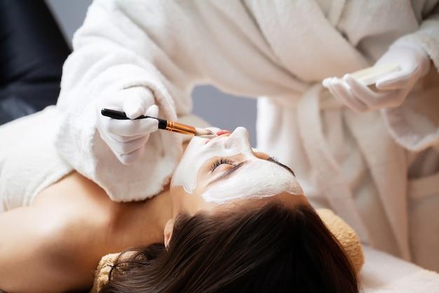 美容師がスパのソファで横になっている女性の顔にマスクを適用します