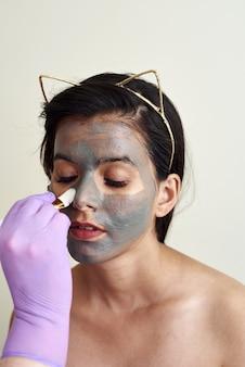 미용사는 고객의 얼굴에 보습 마스크를 적용합니다.